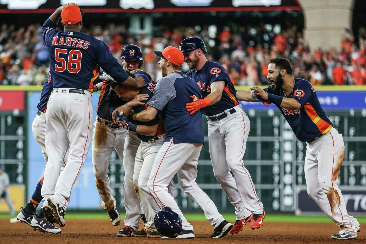 Teammates crowd around Houston Astros catcher Juan Centeno (30) after he hit a single to bring in the winning run as the Houston Astros scored four runs in the ninth inning to beat the Toronto Blue Jays 7-6 Sunday, Aug. 6, 2017 in Houston.