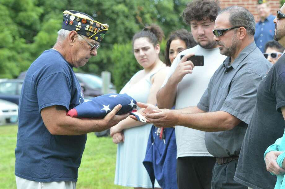 Danny Robinson, son of Navy veteran Robert James Robinson, passes the American flag to Sergeant-at-Arms Dan Caporale to be raised during the Veteran of the Month ceremony honoring the World War 11 veteran for the month of August, on Sunday in Norwalk. The Veteran of the Month ceremony is held at American Legion Post 12. Photo: Alex Von Kleydorff / Hearst Connecticut Media / Norwalk Hour