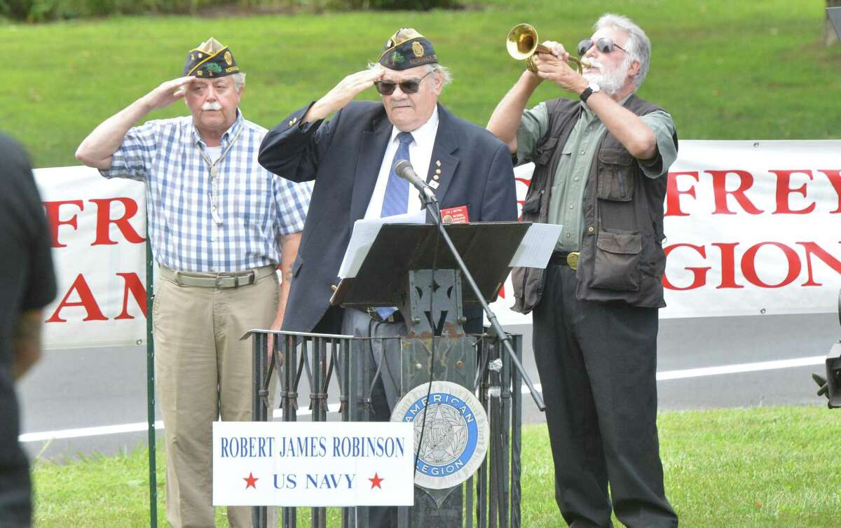 Past Commander Leo Motyke salutes with other Post 12 members as the flag is raised during the Veteran of the Month ceremony honoring the World War 11 Navy veteran Robert James Robinson, veteran for the month of August, on Sunday in Norwalk. The Veteran of the Month ceremony is held at American Legion Post 12.