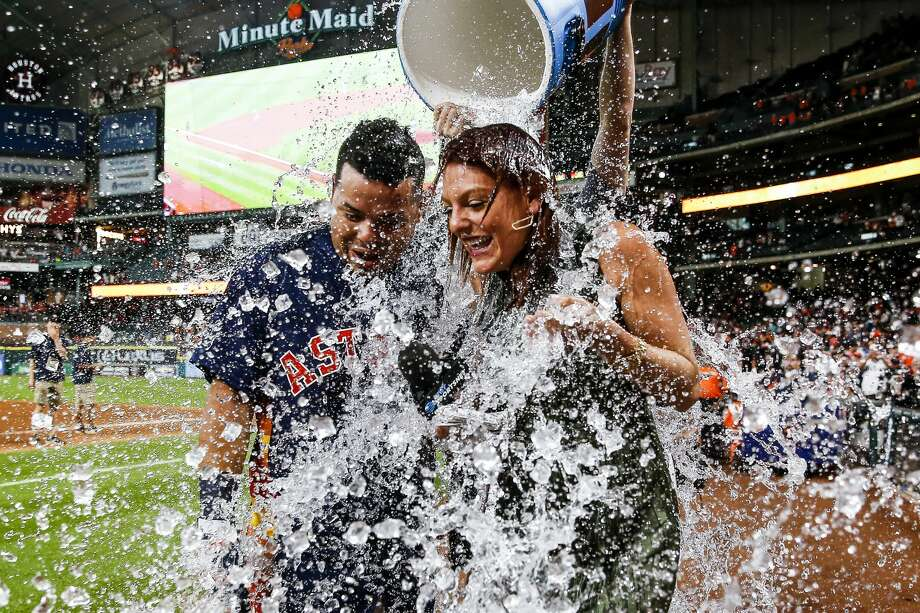 Houston Astros catcher Juan Centeno (30) and AT&T Sportsnet reporter Julia Morales get drenched by starting pitcher Collin McHugh (31) after Centeno hit a walk off single during the ninth inning. The Houston Astros scored four runs in the ninth to beat the Toronto Blue Jays 7-6 Sunday, Aug. 6, 2017 in Houston. ( Michael Ciaglo / Houston Chronicle ) Photo: Michael Ciaglo/Houston Chronicle