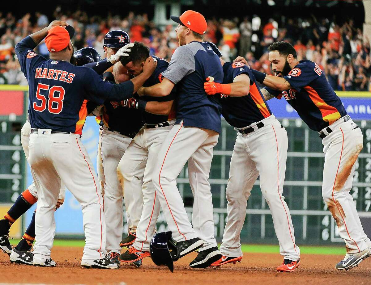 Houston Astros' Juan Centeno, second from left, is mobbed by teammates after his walkoff RBI-single in a baseball game against the Toronto Blue Jays, Sunday, Aug. 6, 2017, in Houston. (AP Photo/Eric Christian Smith)