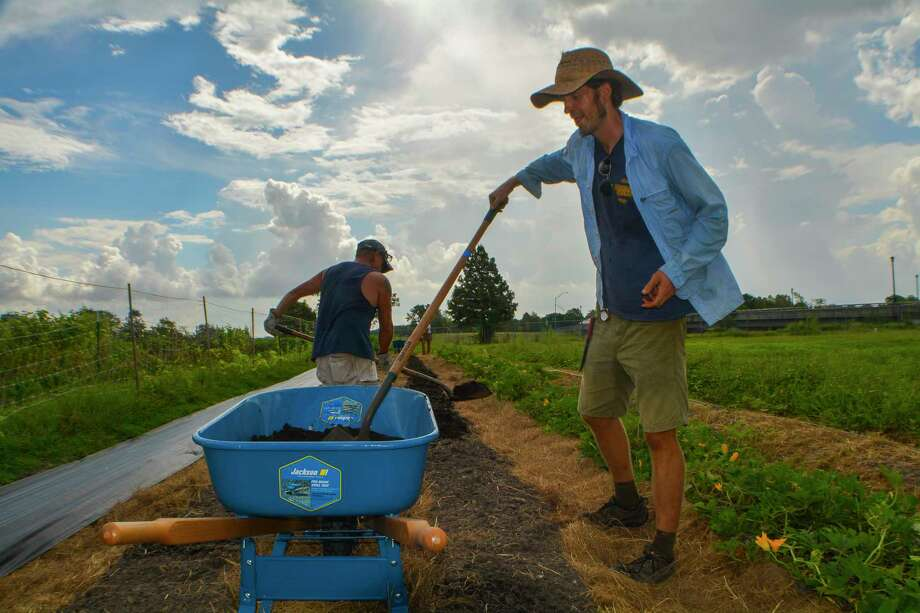 Justin Myers, chief agricultural officer for the nonprofit Recipe for Success, and military veteran Ronnie Wright lay soil as they prep the ground for the farm's fall production at Hope Farms in Sunnyside. Photo: John D. Harden