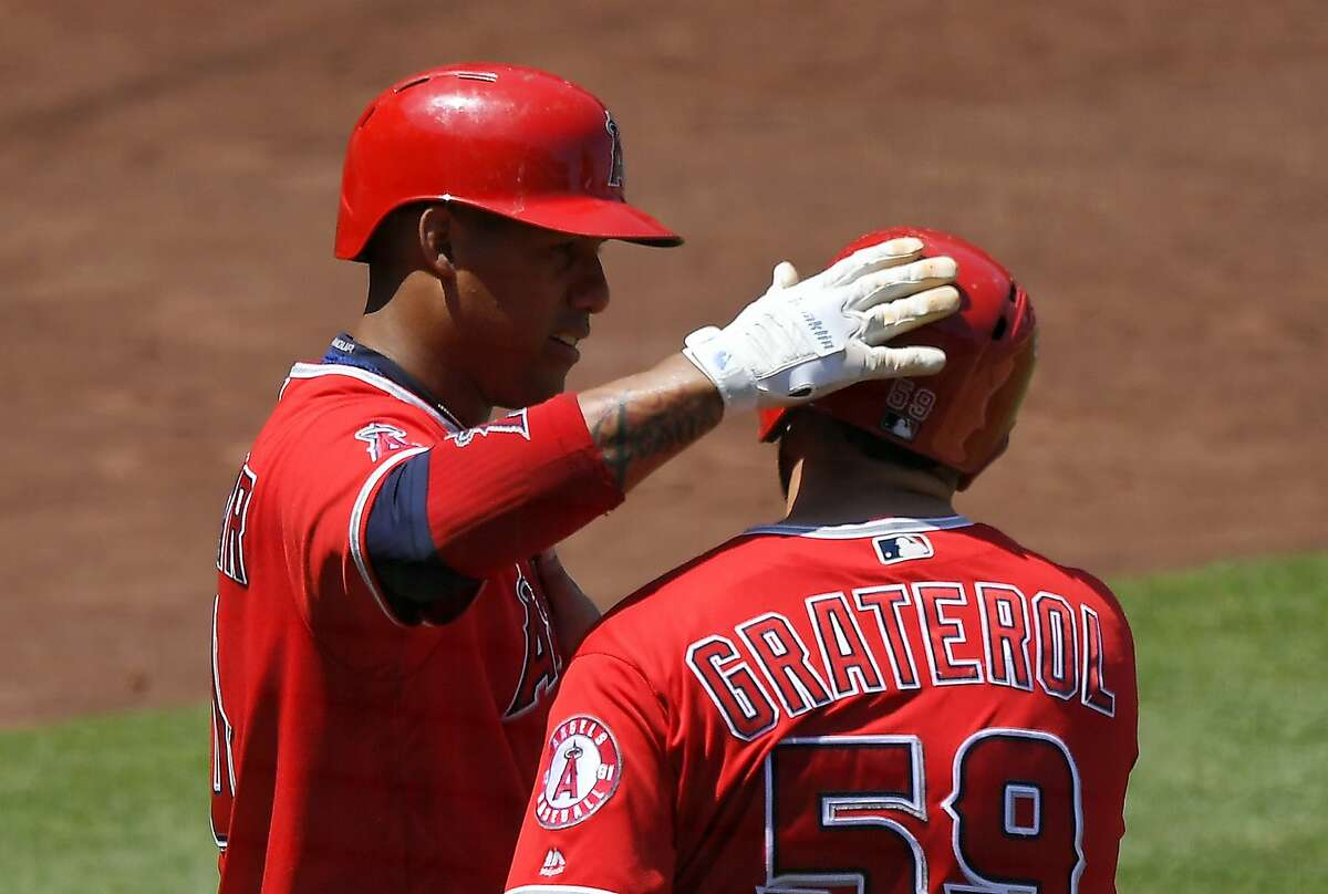 Los Angeles Angels' Juan Graterol, right, gets a pat on the helmet from Yunel Escobar after scoring on a single by Cliff Pennington during the fourth inning of a baseball game against the Oakland Athletics, Sunday, Aug. 6, 2017, in Anaheim, Calif. (AP Photo/Mark J. Terrill)