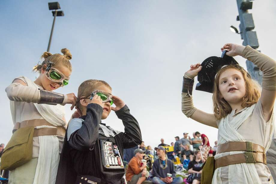 Dressed as Rey from Star Wars: The Force Awakens, Maleah Roth, 9, left, helps put goggles onto her little brother, Blaine Roth, 5, dressed as Darth Vader, as Eliana Kirkham, 6, right, dons his mask while also dressed as Rey during Star Wars night at Dow Diamond on Saturday. Photo: (Danielle McGrew Tenbusch/for The Daily News)
