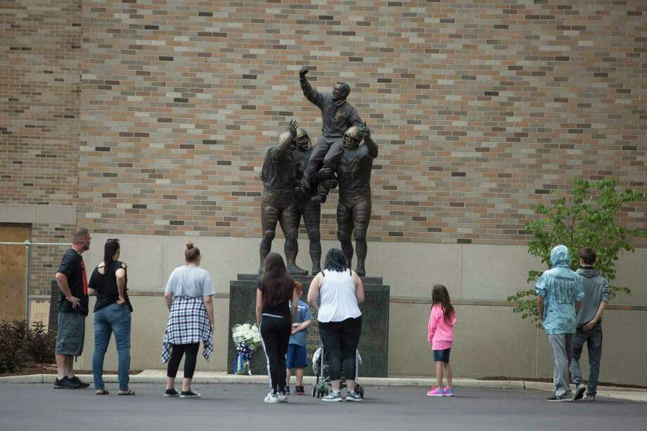 Fans visit the Ara Parseghian statue outside the Ara Parseghian gate at Notre Dame Stadium, Sunday, Aug. 6, 2017, in South Bend, Ind. The University of Notre Dame held a Mass and memorial celebration for Parseghian who died on August 2, 2017. Parseghian led Notre Dame to national football titles in 1966 and 1973. (Santiago Flores/South Bend Tribune via AP) ORG XMIT: INSBE904 Photo: Santiago Flores / South Bend Tribune