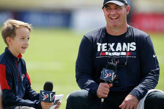 """Texans """"kid reporter"""" Luke Vandermeer catches coach Bill O'Brien at ease during a training camp get-together last week."""