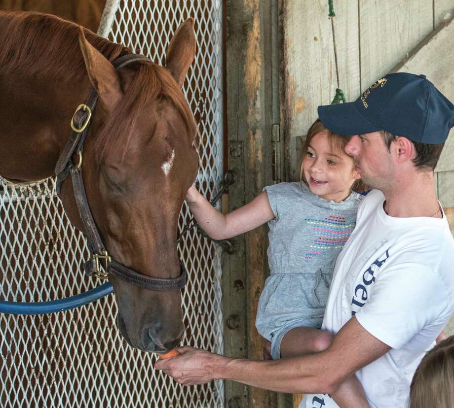 Jockey Florent Geroux holds his daughter Olivia,5, as he feeds Whitney Stakes winner Gun Runner carrots at the Oklahoma Training center Sunday Aug. 6, 2017 in Saratoga Springs, N.Y.  (Skip Dickstein/Times Union) Photo: SKIP DICKSTEIN