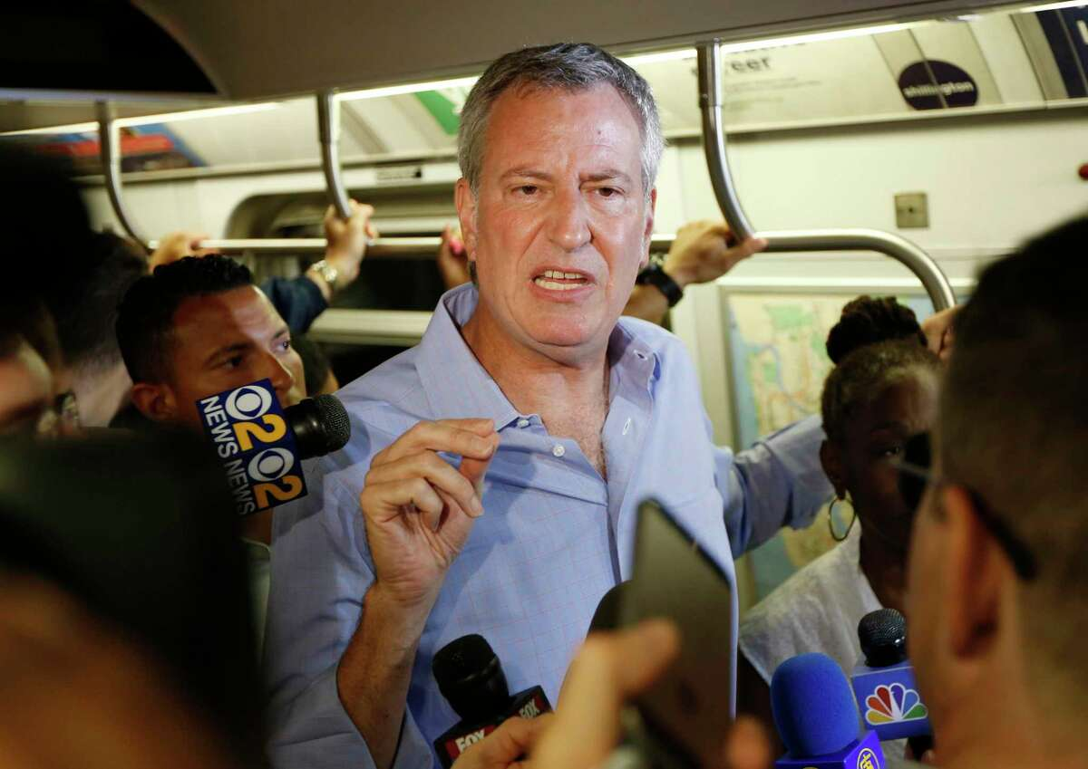 FILE - In this July 23, 2017 file photo, New York Mayor Bill de Blasio talks to reporters on the subway in New York. De Blasio wants to tax the wealthiest 1 percent of New Yorkers to fund repairs and improvements to the beleaguered subway system. The proposal comes as the mayor and Gov. Andrew Cuomo continue to squabble over who is responsible for paying for repairs to the nation's largest system. (AP Photo/Seth Wenig, File) ORG XMIT: NYR102