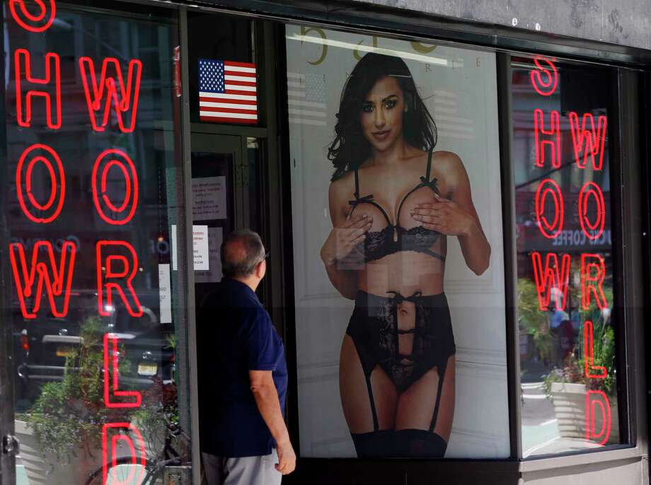 In this Thursday, Aug. 3, 2017, photo, a man looks at a poster in the window of Show World Center, one of Times Square's last surviving pornography businesses, in New York. The city's two-decade legal war on storefront businesses like this one may have reached a new tipping point. While many of the grimy attractions were swept out of years ago, especially ones in retail-filled, neon-lit Times Square, the state's highest court recently issued a ruling that could force the surviving ones to shut down. (AP Photo/Kathy Willens) ORG XMIT: NYR407 Photo: Kathy Willens / Copyright 2017 The Associated Press. All rights reserved.