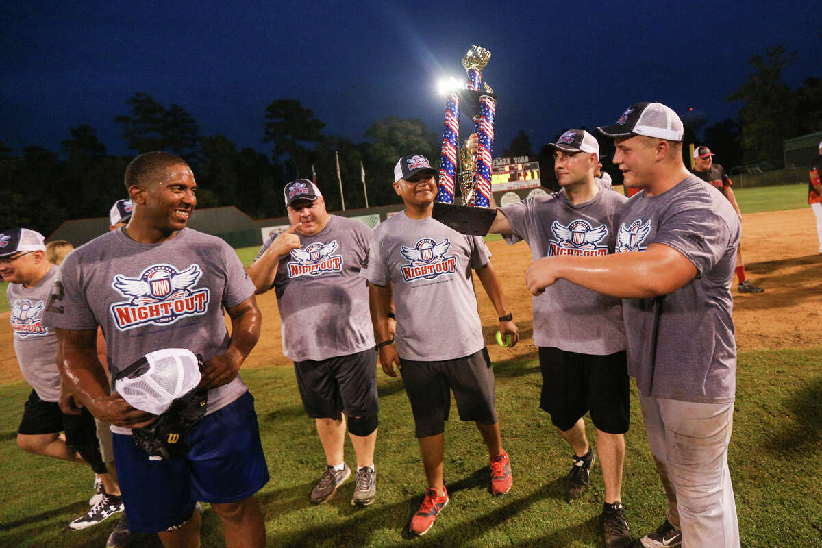 The Montgomery County Sheriff's Office celebrate their win in the Boots vs Badges softball game against The Woodlands Fire Department on Sunday at McCullough Junior High School.