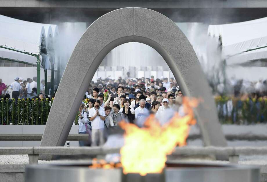 """People offer prayers at the Peace Memorial Park in Hiroshima, western Japan, Sunday, Aug. 6, 2017, to mark the 72nd anniversary of the world's first atomic bombing that killed 140,000 people in 1945. Hiroshima's appeal of """"never again"""" on the 72nd anniversary has acquired renewed urgency as North Korea moves ever closer to acquiring nuclear weapons. (Ryosuke Ozawa/Kyodo News via AP) ORG XMIT: TKH801 Photo: Ryosuke Ozawa / Kyodo News"""