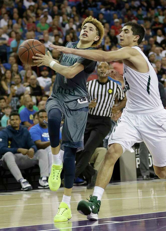 FILE - In this March 26, 2016, file photo, Chino Hills' LaMelo Ball, left, goes to the basket against De La Salle's Jordan Ratinho during the second half of the CIF boys' Open Division high school basketball championship game, in Sacramento, Calif. Ball was among the top recruits who played in tournaments around Las Vegas the last week of July during the live recruiting period for college coaches. (AP Photo/Rich Pedroncelli, File) ORG XMIT: NY252 Photo: Rich Pedroncelli / Copyright 2016 The Associated Press. All rights reserved. This m