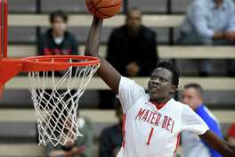 FILE - In this Feb. 4, 2017, file photo, Mater Dei's Bol Bol dunks against St. Augustine, in Santa Ana, Calif. Bol was among the top recruits who played in tournaments around Las Vegas the last week of July during the live recruiting period for college coaches. (Bill Alkofer/The Orange County Register via AP, File) ORG XMIT: CAANR201