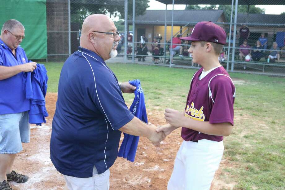 Caleb Cox receives a Director's Tournament T-shirt from a Pony official after a game back in June. Cox took the loss on the hill in Saturday afternoon's showdown with Deer Park at the Souuth Zone Tournament. Photo: Robert Avery