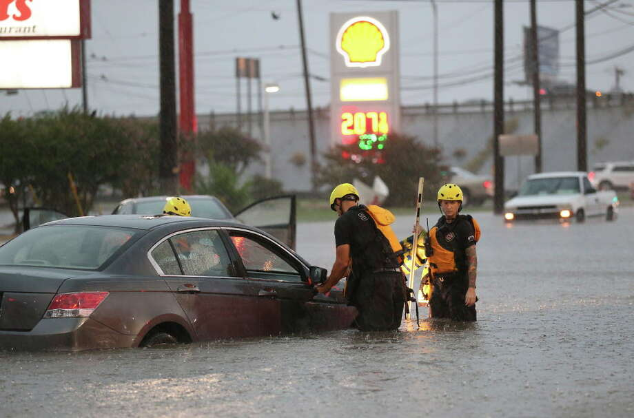 San Antonio Fire Department personnel check out vehicles stuck in high water at Marbach Road and Loop 410, Monday, August 7, 2017. Photo: JERRY LARA, San Antonio Express-News / San Antonio Express-News