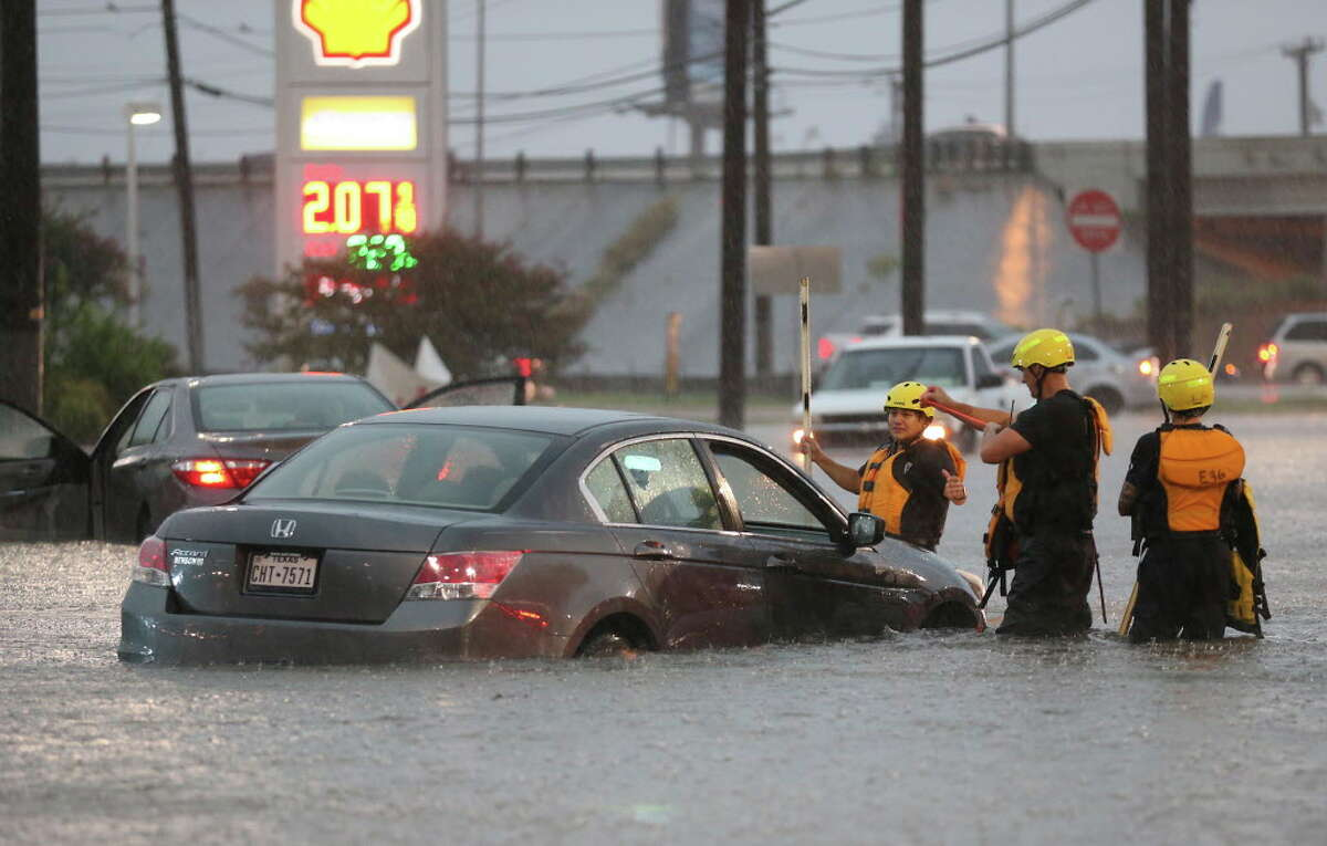 August 2017 San Antonio Fire Department personnel check out flooded cars at Marbach Road and Loop 410 on Aug. 7.