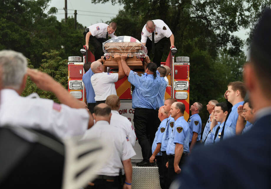 Firefighters lower Jay Hinkie's casket from the back of a fire truck during the Silsbee firefighter's funeral on Sunday. Hinkie was killed last week when he was struck by a car while working a rollover accident. Photo taken August, 06, 2017   Guiseppe Barranco/The Enterprise Photo: Guiseppe Barranco, Photo Editor / Guiseppe Barranco ©