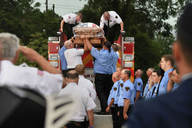 Firefighters lower Jay Hinkie's casket from the back of a fire truck during the Silsbee firefighter's funeral on Sunday. Hinkie was killed last week when he was struck by a car while working a rollover accident. Photo taken August, 06, 2017   Guiseppe Barranco/The Enterprise