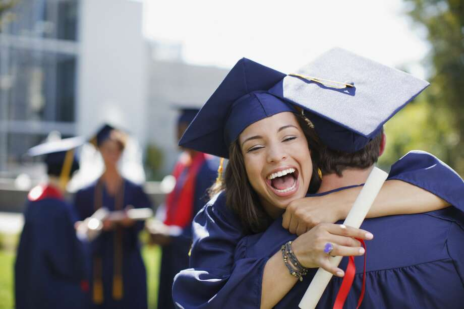 Smiling graduates hug outdoors. Click through to see which Houston colleges earn the most after school. Photo: Paul Bradbury/Getty Images