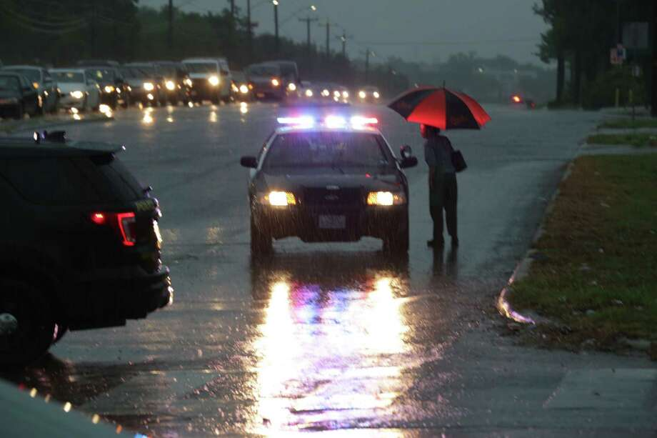 Police ask a woman where she is going as police vehicles block north bound traffic on Babcock Rd at Callaghan due to high water on Monday Aug. 7, 2017. Photo: Bob Owen, San Antonio Express-News / San Antonio Express-News