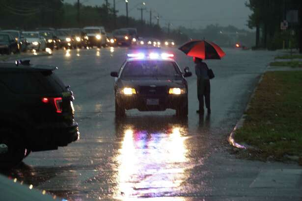 Police ask a woman where she is going as police vehicles block north bound traffic on Babcock Rd at Callaghan due to high water on Monday Aug. 7, 2017.