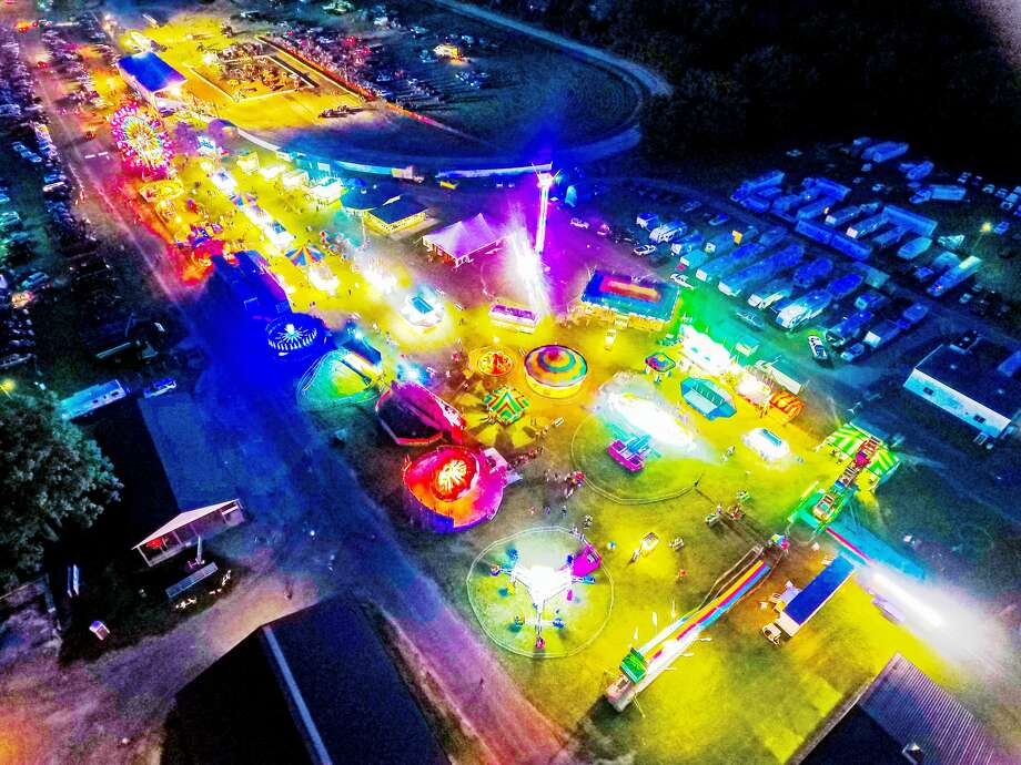 A festive evening at the Huron Community Fair is captured from above with rides, games and food spread throughout the fairgrounds. Photo: Tyler Leipprandt, Michigan Sky Media/For  The Tribune