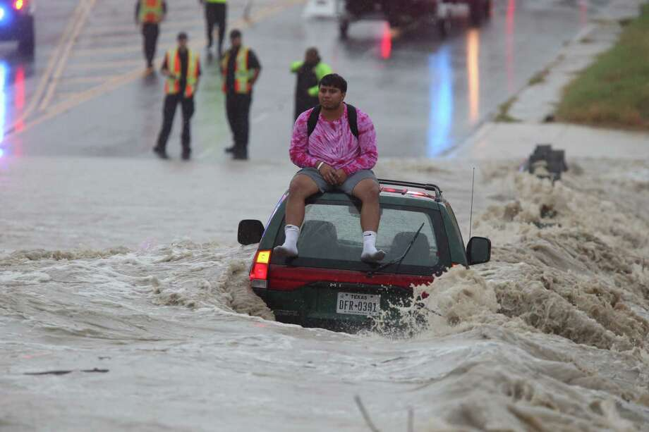 Authorities on Monday rescued two divers whose cars became submerged less than a mile apart from each other. At around 11 a.m., emergency crews worked to rescue this driver who was trapped on the roof on his vehicle at Pinn Road and State Hwy. 151. Photo: Jerry Lara, San Antonio Express-News / 2017 San Antonio Express-News