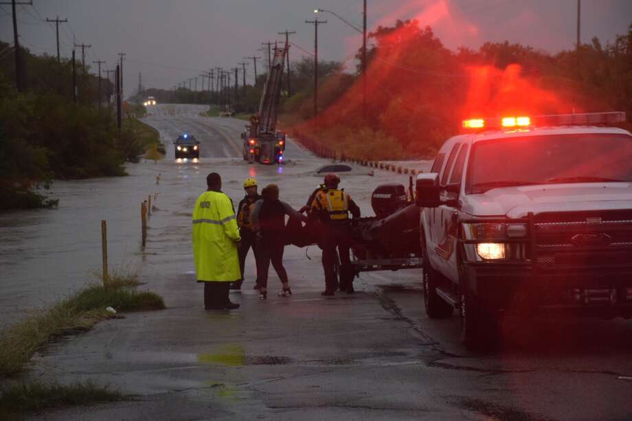 Authorities on Monday rescued two drivers whose cars became submerged less than a mile apart from each other. Photo: Caleb Downs / San Antonio Express-News