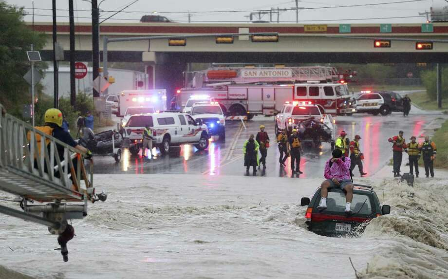 San Antonio Fire Department personnel rescue a man trapped on top of his submerged vehicle at a low water crossing on Pinn Road by SH151, Monday, August 7, 2017. Photo: JERRY LARA / San Antonio Express-News / San Antonio Express-News