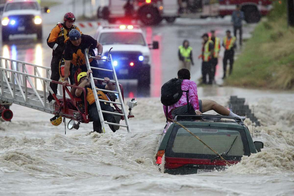 August 2017 San Antonio Fire Department personnel rescue a man trapped on top of his submerged vehicle at a low water crossing on Pinn Road  Aug. 7 after rains caused localized flooding in the area.