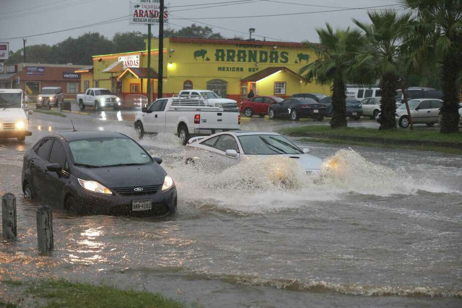 Traffic moves around a vehicle stalled in high water at the intersection of West Military Drive and Westbriar, Monday, August 7, 2017. Photo: JERRY LARA / San Antonio Express-News / San Antonio Express-News