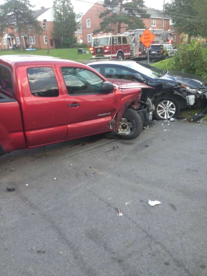 A stolen pickup truck crashed into a garbage truck, the a parked car on Watt Street in Schenectady on Friday, Aug. 4, 2017. Photo: State Police