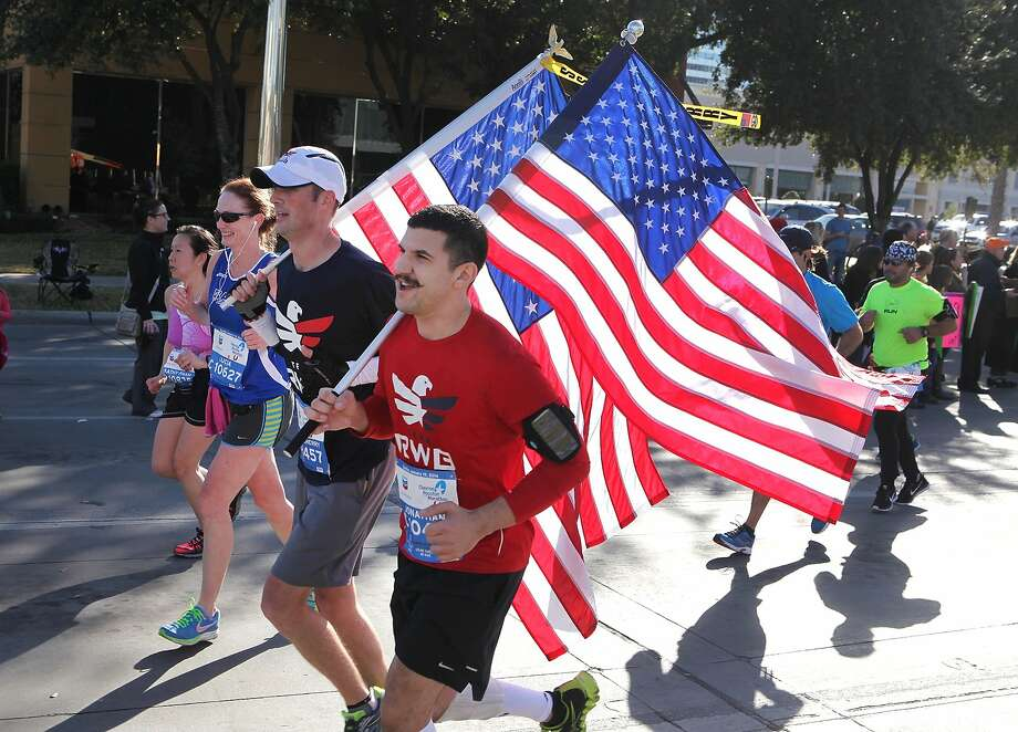 Runners carry American flags during the 2014 Houston Marathon. Photo: Alan Warren, Houston Community Newspapers