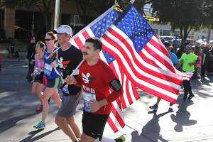 Runners carry American flags on Post Oak Boulevard during the 2014 Houston Chevron Marathon in Houston.
