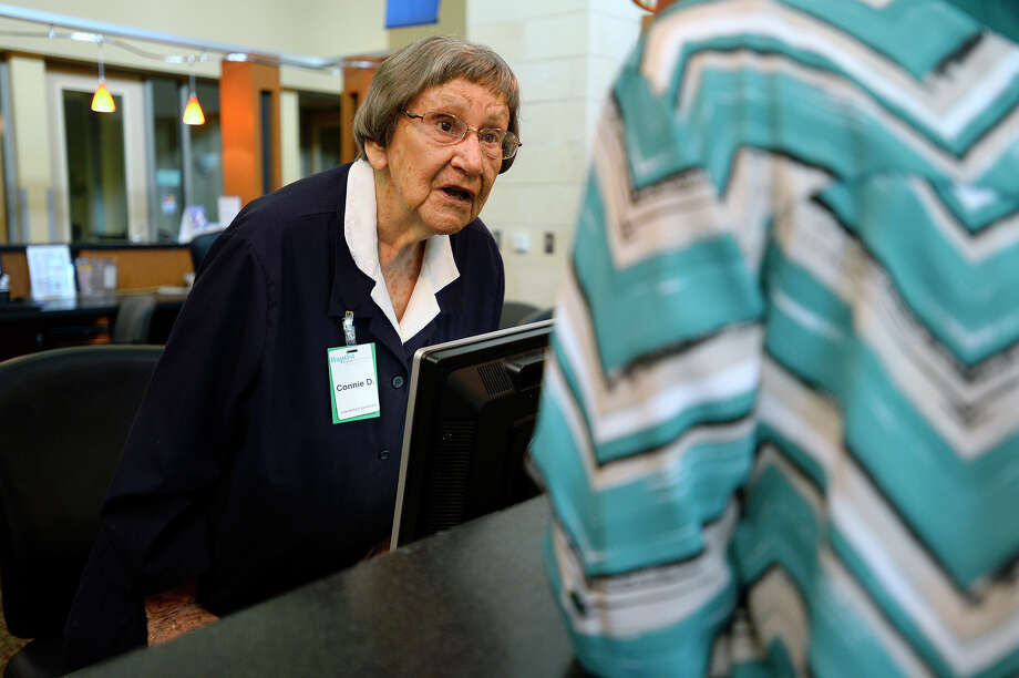 Connie Dickinson talks with a visitor at the front desk while volunteering at Baptist Hospital on Saturday. The 100-year-old Dickinson has worked over 15,000 hours since she began volunteering at the hospital nearly 30 years ago.  Photo taken Saturday 8/5/17 Ryan Pelham/The Enterprise Photo: Ryan Pelham / ©2017 The Beaumont Enterprise/Ryan Pelham
