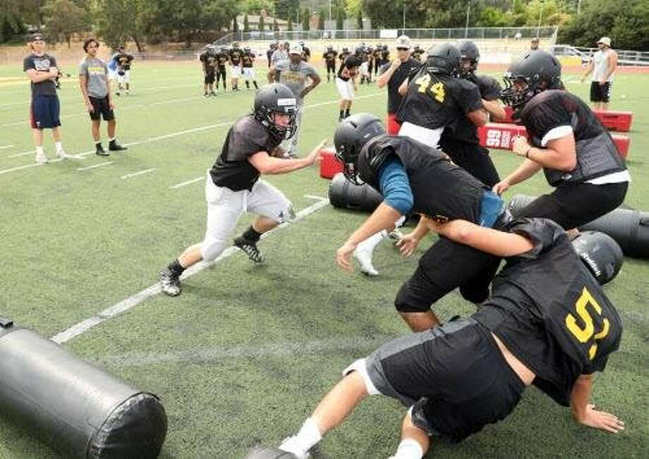 Novato High School senior Colton Carr runs the ball during drills at football practice in Novato, Calif. on Thursday, August 3, 2017. Photo: Scott Strazzante, The Chronicle