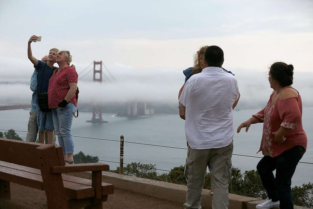 Tourists view the fog surrounding the Golden Gate bridge on Friday, August 4, 2017, in Marin County, Calif.