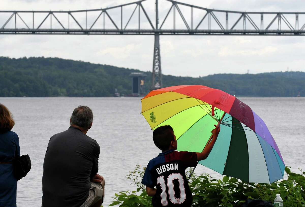 Noah Gibson, 9, plays with an umbrella as he and his grandfarther, Tom, watch as a A 130 foot tall steam generator that was assembled at the Port of Coeymans is transported down the Hudson River past Rip Van Winkle Bridge on Monday, Aug. 7, 2017, in Catskill, N.Y. The generator was built for plant in New Jersey. (Will Waldron/Times Union)