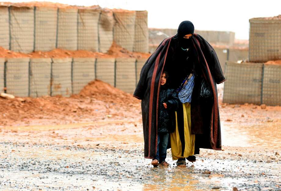 A Syrian refugee from the informal Rukban camp, which lies in no-man's-land off the border between Syria and Jordan in the remote northeast, walks in the rain, as she shelters a young child outside a UN-operated medical clinic immediately on the Jordanian side. Photo: KHALIL MAZRAAWI/AFP/Getty Images