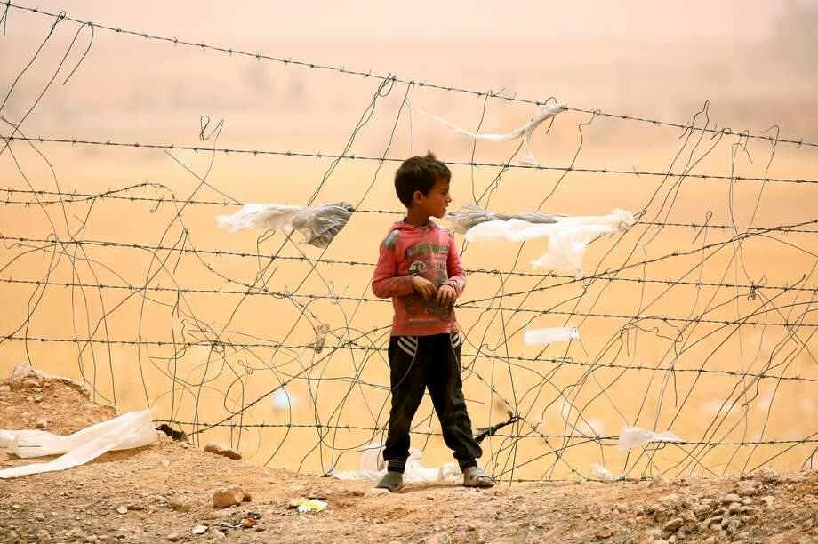 A displaced Syrian boy who fled the Islamic State group stronghold of Raqa stands near a fence during a sandstorm at a temporary camp in a northern Syrian village. Photo: DELIL SOULEIMAN/AFP/Getty Images