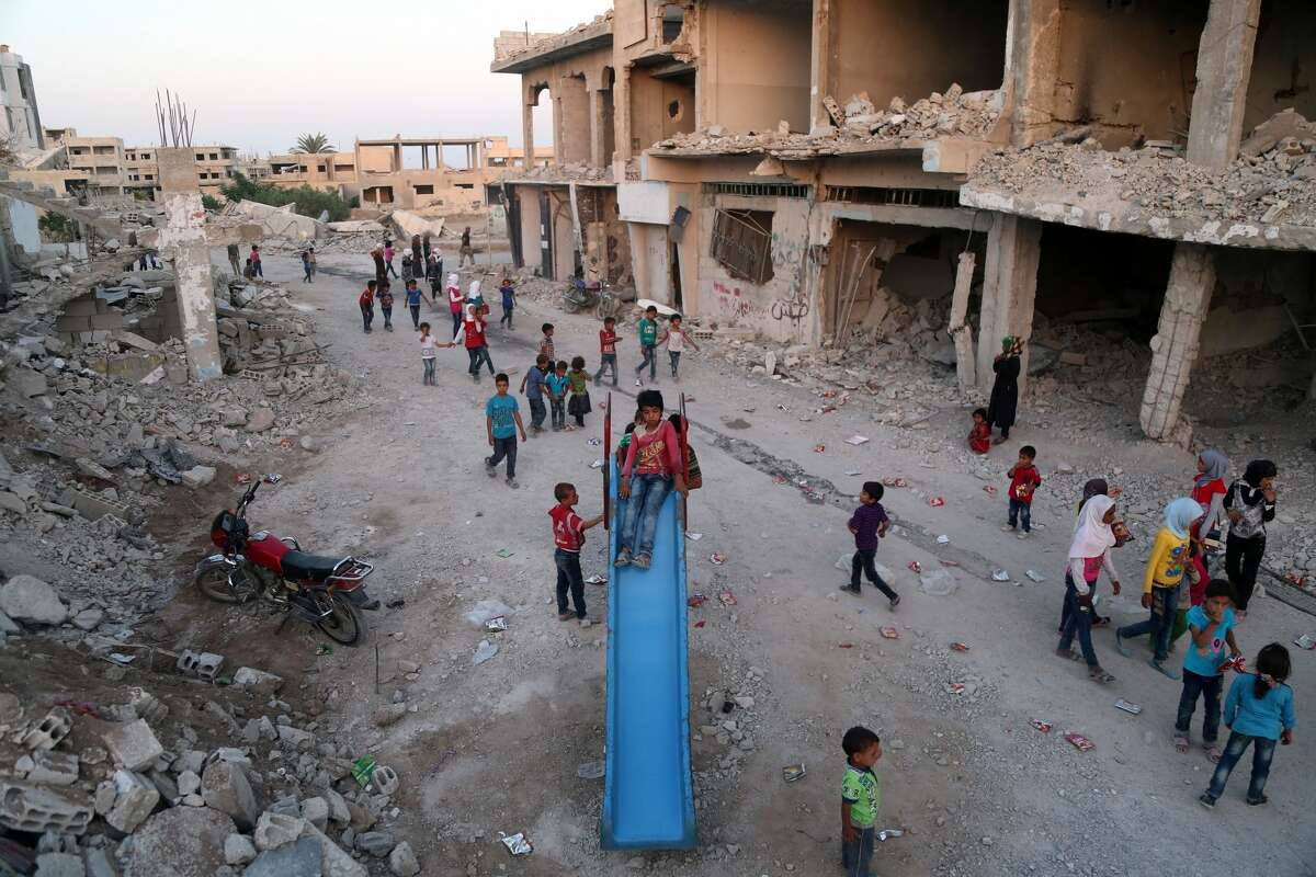 Syrian children, who fled their homes in Ghouta's al-Marj town, play amidst the debris of buildings in the town of al-Nashabiyah in the eastern Ghouta region, a rebel stronghold east of the capital Damascus.