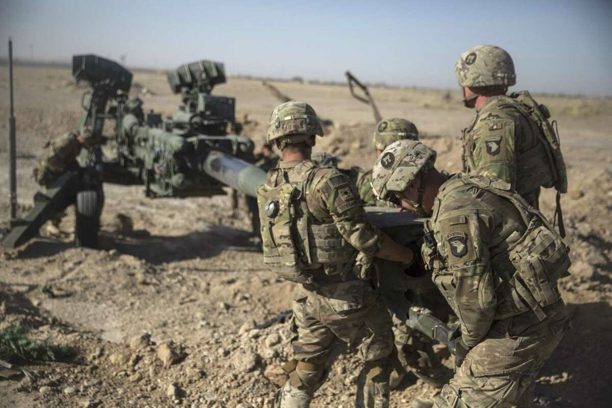 U.S. soldiers maneuver an M777 howitzer so it can be towed into position at Bost Airfield, Afghanistan. A reader recommends that the government reinstitute the draft.