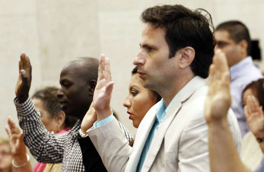 Dasiel Rodriquez, of Cuba, right, Ingrid Sharpe of Mexico, and Robert Kipkorir Rono of Kenya, were among 33 immigrants who recited the Oath of Allegiance to the United States of America during a naturalization ceremony at the federal courthouse in Jackson, Miss. July 6. Trump and two senators propose to cut legal immigration in half. Photo: Rogelio V. Solis /Associated Press / Copyright 2017 The Associated Press. All rights reserved.