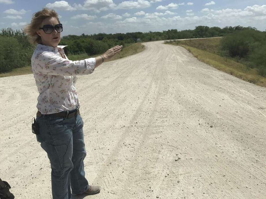 Marianna Trevino-Wright of the National Butterfly Center stands on a levee in the Rio Grande Valley where the wall could be built. Photo: Aaron Nelson / San Antonio Express-News / San Antonio Express-News