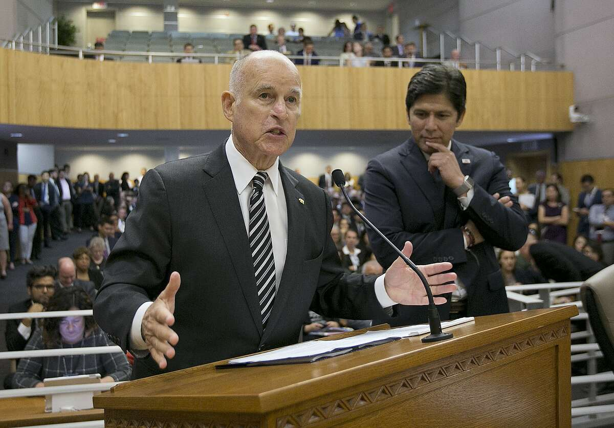 FILE - In this July 13, 2017 file photo, California Gov. Jerry Brown, left, flanked by Senate President Pro Tem Kevin de Leon, D-Los Angeles, urges members of the Senate Environmental Quality Committee to approve a pair of bills to extend state's cap and trade program during a hearing of the Senate Environmental Quality committee, in Sacramento, Calif. As his fourth and final term winds down Brown will spend the final 17 months in office working on California's housing crisis and fighting for ambitious projects to build a high-speed rail system and re-engineer California's water system. (AP Photo/Rich Pedroncelli, file)
