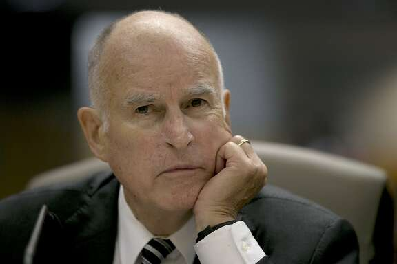 FILE - In this July 13, 2017 file photo, Calif., Gov. Jerry Brown listens as members of the Senate Environmental Quality Committee discuss a pair of climate change bills he supports, in Sacramento, Calif. California lawmakers are nearing a high-stakes decision that will decide the fate of a climate initiative that Brown holds up as a model to be replicated around the world to confront rising global temperatures. A vote is set for Monday on whether to give another decade of life to California's cap-and-trade program. (AP Photo/Rich Pedroncelli, File)