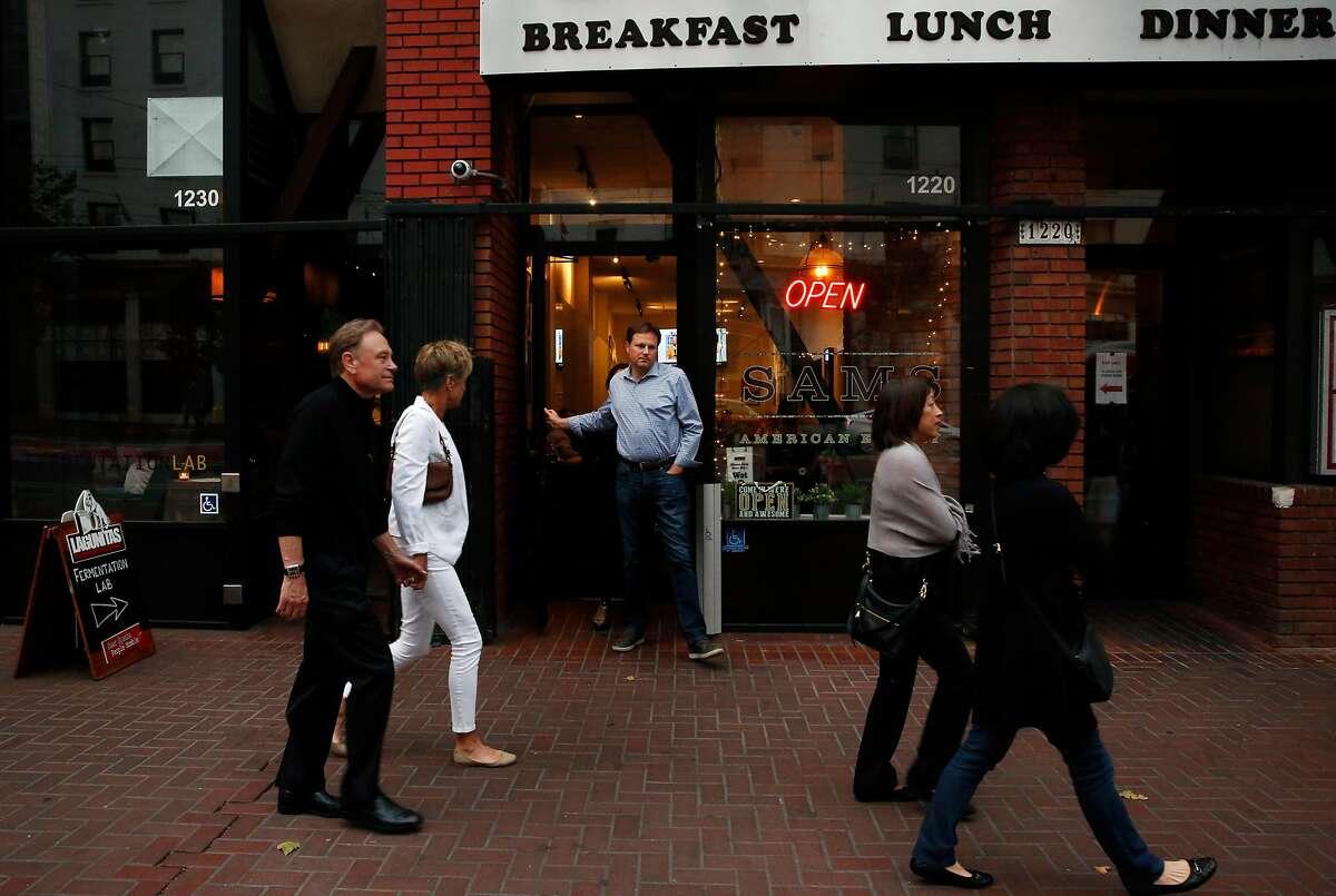 People walk past Sams American Eatery.
