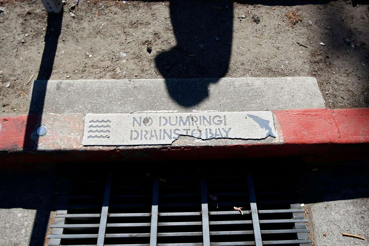 Lupe Quinones' shadow is seen near a storm drain as she walks through her neighborhood in Redwood City, CA Friday September 6, 2013. Lupe Quinones is a participant in a Stanford research project that has senior citizens walk around their neighborhoods and take photos and document problematic spots to collect data and advocate for changes on civic level.