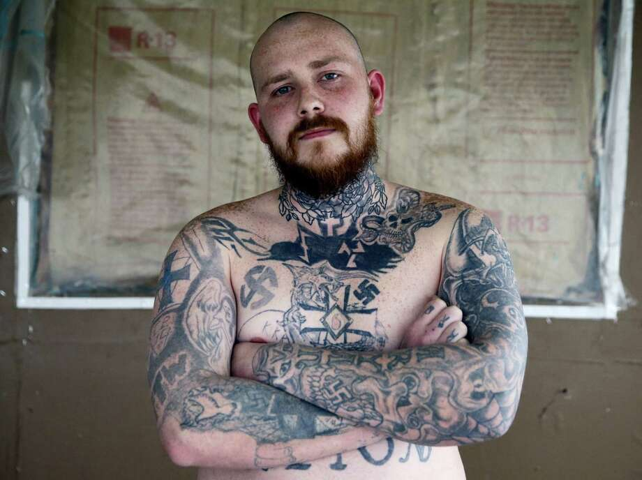 In this Thursday, Jan. 12, 2017 photo, Shane Johnson displays some of his tattoos as he poses in his home in Tippecanoe, Ind. Johnson was born into extremism is in the process of covering some of his racist tattoos with new ones and wears long sleeves to hide remnants of his past he regrets. His father and many of his father's relatives were part of the Klan, he said, so there was only one real way for him to go as a youth. (AP Photo/Michael Conroy) Photo: AP / Copyright 2017 The Associated Press. All rights reserved.