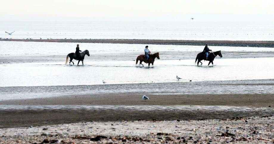File photo: Left to right, Jenny Corso, of Derby, Lucy Reynolds, of Seymour, and Trish Perrotti, of Orange, ride horses at Silver Sands State Park in Milford during low tide. Photo: (Arnold Gold/New Haven Register)